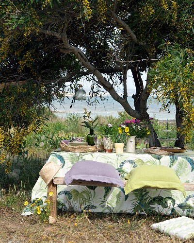 Idyllic, picturesque dining area under tree with sea view and table set in rustic style