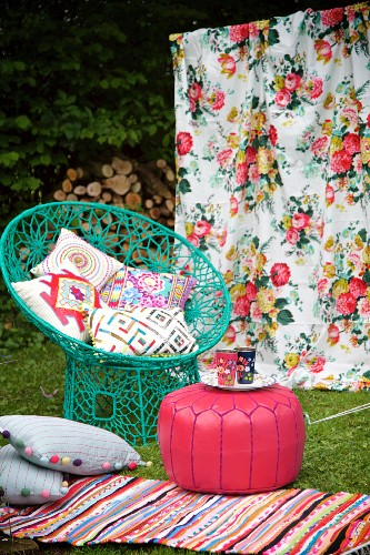 Seating and striped rug on lawn, floral cloth hung as backdrop