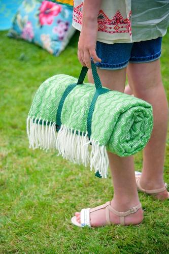 Rolled, green picnic blanket held by girl in garden