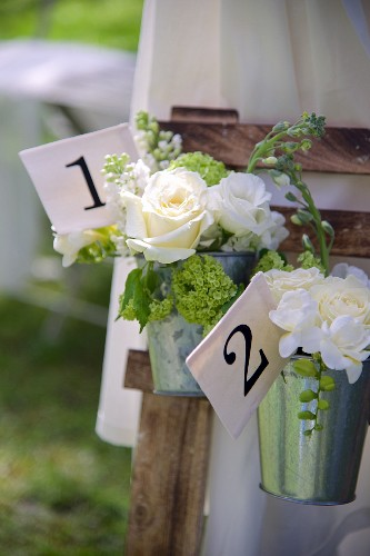 Bouquets of white roses in zinc buckets with numbered labels
