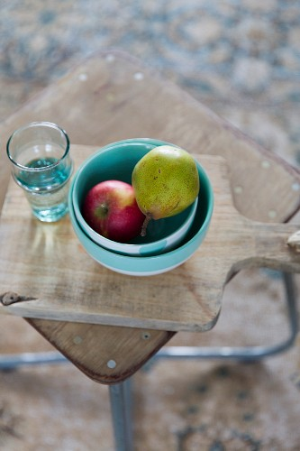 Fruit in ceramic bowls and glass of water on chopping board on side table