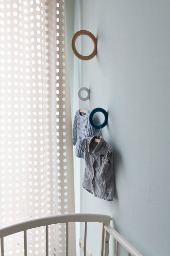 Ring brackets in different colours mounted on wall and child's clothing hung from wooden coat hanger