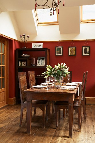 Traditional dining set and exotic-wood shelves against red-painted wall below skylights