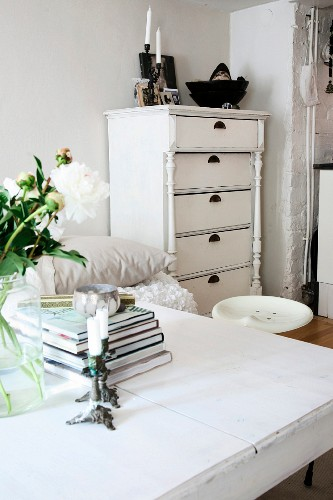 View across table to white chest of drawers with turned columns on front