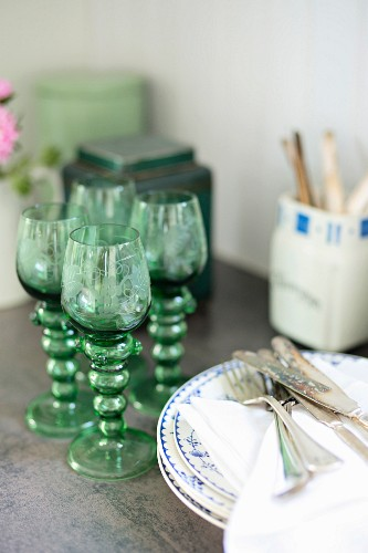 Old, German roemer wine glasses next to stack of plates and cutlery