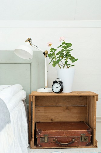 Retro table lamp and geranium in white pot on wooden crate used as bedside table holding leather suitcase