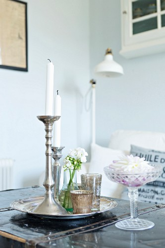 White candles in silver candlesticks on tray and white flower in crystal dish