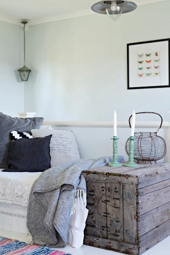 White candles in candlesticks on vintage wooden crate next to daybed in corner of simple room