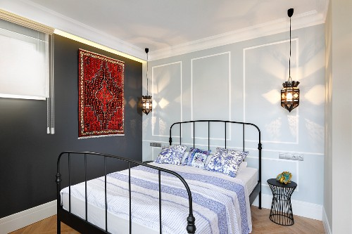 Double bed with black, metal lattice frame, Moroccan-style rug on dark grey wall and pendant lamp in bedroom