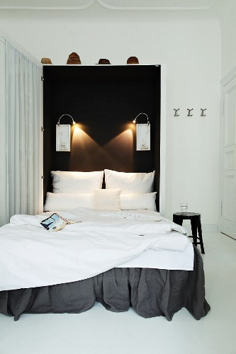 Foldaway bed with dark grey valance and white bed linen against black wall with reading lamps