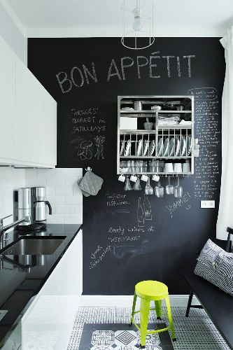 Kitchen with glossy fronts, decorative black and white floor tiles and chalkboard wall