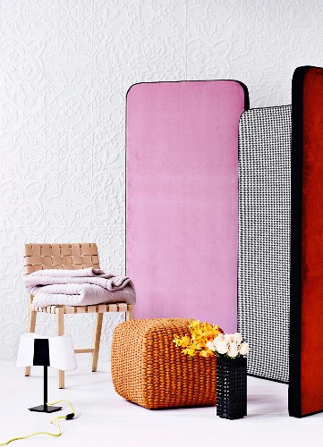 Colourful screens, woven leather chair, cane pouffe and vase of flowers