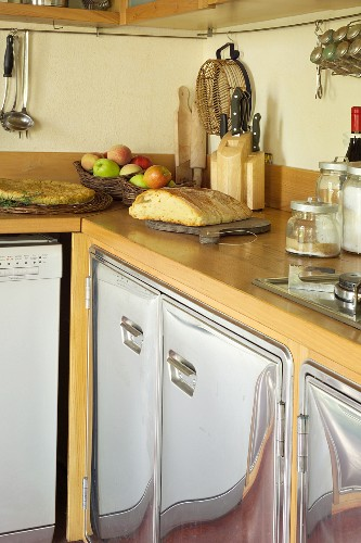 Detail of kitchen counter with curved stainless steel fronts and wooden worksurface