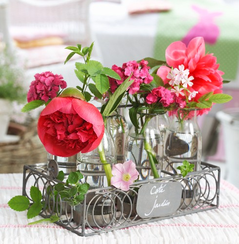 Retro milk bottles used as vases for peonies and other garden flowers in ornamental, grey wire bottle carrier