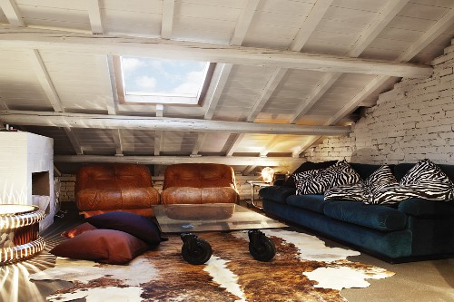 Vintage seating area with worn leather armchairs, glass table on rubber castors and iconic light sculptures in attic room