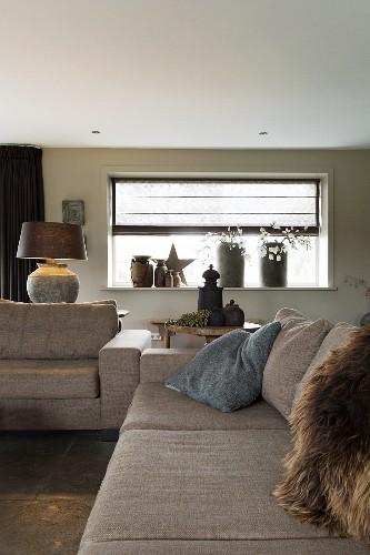 Grey sofa set in front of Christmas arrangement on windowsill