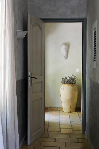Offene Tür zum gefliesten Eingangsbereich mit Terracottatopf