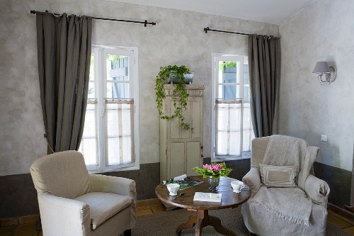 Zwei Sessel mit Hussen an rundem Biedermeiertisch und von Fenstern mit Vorhang flankierter, alter Schrank mit Efeupflanze
