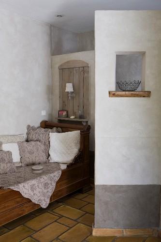 Antike Sofabank mit massiven Seitenteilen vor der Trennwand zur Toilette und Sichtschutzmauer mit dekorativem Fensterchen vor dem Waschtisch