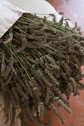 Getrocknete Lavendelblüten in Leinensack auf Polsterhocker