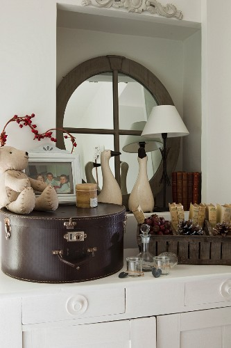 Vintage hat box arranged on white cabinet with ornaments and round, wood-framed mirror in niche
