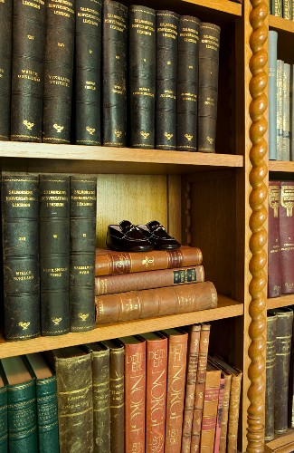 Detail of bookshelves with carved, wooden ornamentation and antiquarian books with gilt-embossed spines