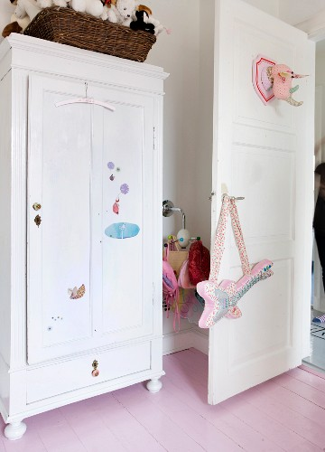 White, farmhouse wardrobe with nursery decorations next to fabric guitar hanging on open door