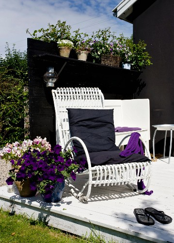 White-painted bamboo chair next to potted violas and petunias on sunny terrace against dark screen