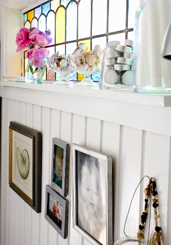 Pictures on white, wood-clad wall below stained-glass transom window with tealight holders and glass dishes on windowsill
