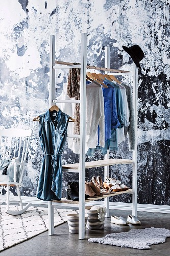 DIY wardrobe made of ladder shelf with clothes rail and compartments for shoes, black and white artistic wall design