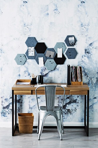 Honeycomb-shaped DIY pin board above desk with vintage chair