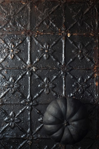 Black pumpkin on metal surface