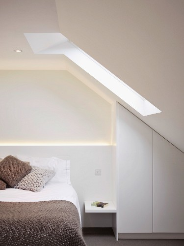 Knitted cushions and blankets in natural shades on bed in purist attic room with fitted wardrobe below sloping ceiling