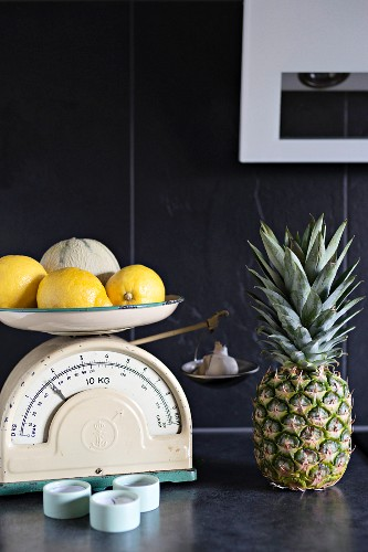 Lemons and melon on vintage kitchen scales on dark grey surface