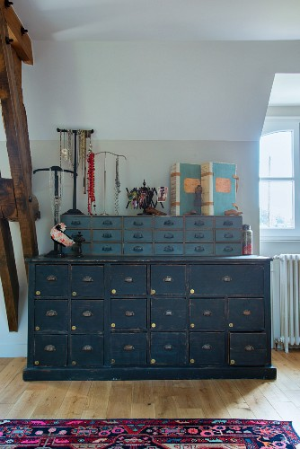 Blue-grey vintage chest of drawers with smaller set of drawers on top, jewellery stands and vintage folders in attic room