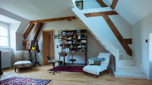 Pleasant interior in double-height attic room with winding wooden staircase painted white