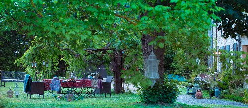 Set table below chestnut trees outside country house