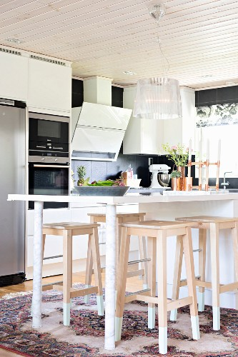 Modern counter-height table and wooden bar stools in open-plan kitchen