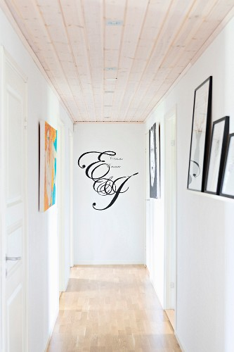Narrow hallway with wooden floor and ceiling and motto written on end wall