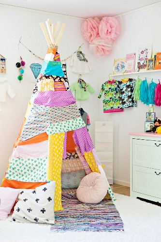 Teepee made from colourful and patterned fabric remnants in front of child's clothing and flower decorations hung on wall in corner