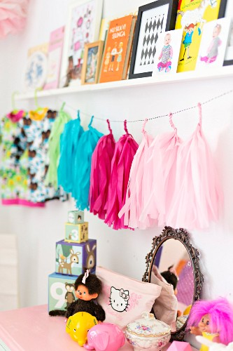 Toys on top of pale chest of drawers below string of colourful tassles and pictures on shelf