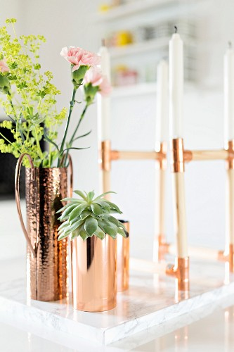 White candles in candelabra next to succulent and flowers in copper vases