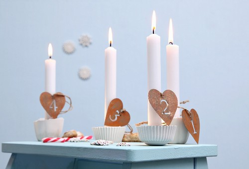 Advent candle holders for single candles made from silicone muffin cases, plaster and numbers on heart-shaped pendants