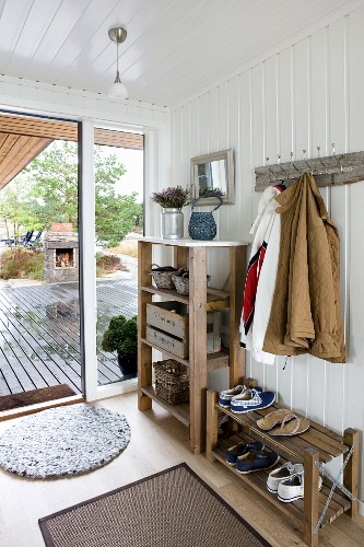 Open-plan cloakroom; shoe rack, clothing hung from coat pegs on white wooden wall and view through open terrace doors in background