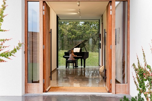 View into foyer with girl playing grand piano and glass wall with view of garden