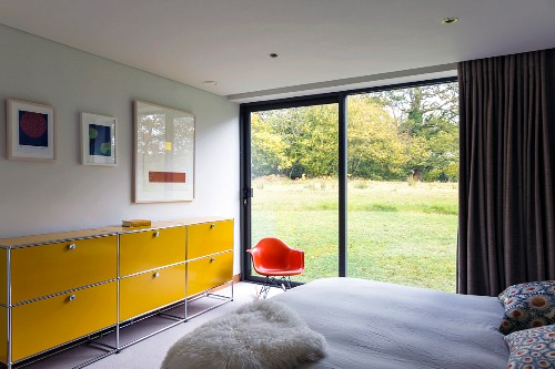 Bedroom with yellow, steel-tube sideboard next to orange, classic shell chair next to glass wall with view of landscaped garden