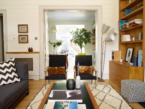 Blick über Couchtisch auf Sessel mit schwarzem Bezug, seitlich Stehleuchte, im Fiftiesstil, vor offenen Flügeltüren