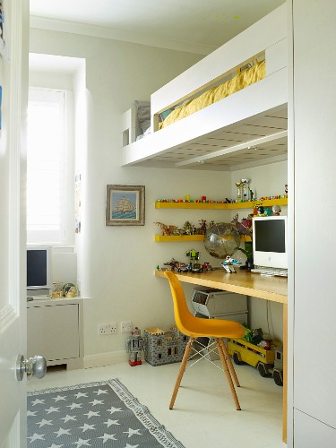 Yellow classic chair in front of floating desk below modern loft bed in child's bedroom