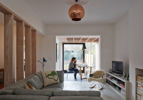 Corner sofa and classic rocking chair with fur blanket; woman and child in conservatory extension with dining area and view of garden