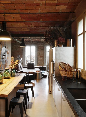 Metal chairs at dining table in open-plan kitchen area below brick ceiling in open-plan interior
